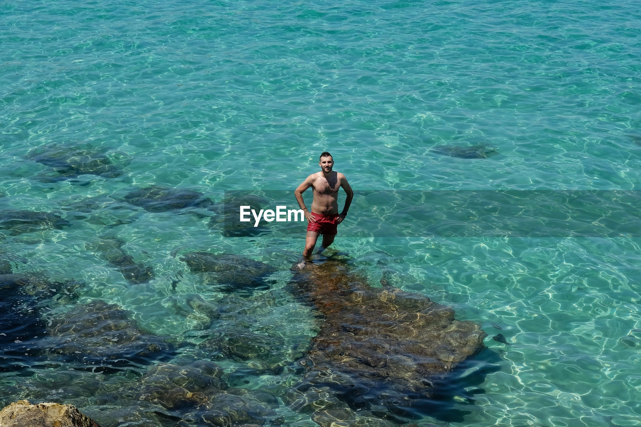 FULL LENGTH OF SHIRTLESS YOUNG MAN IN SEA