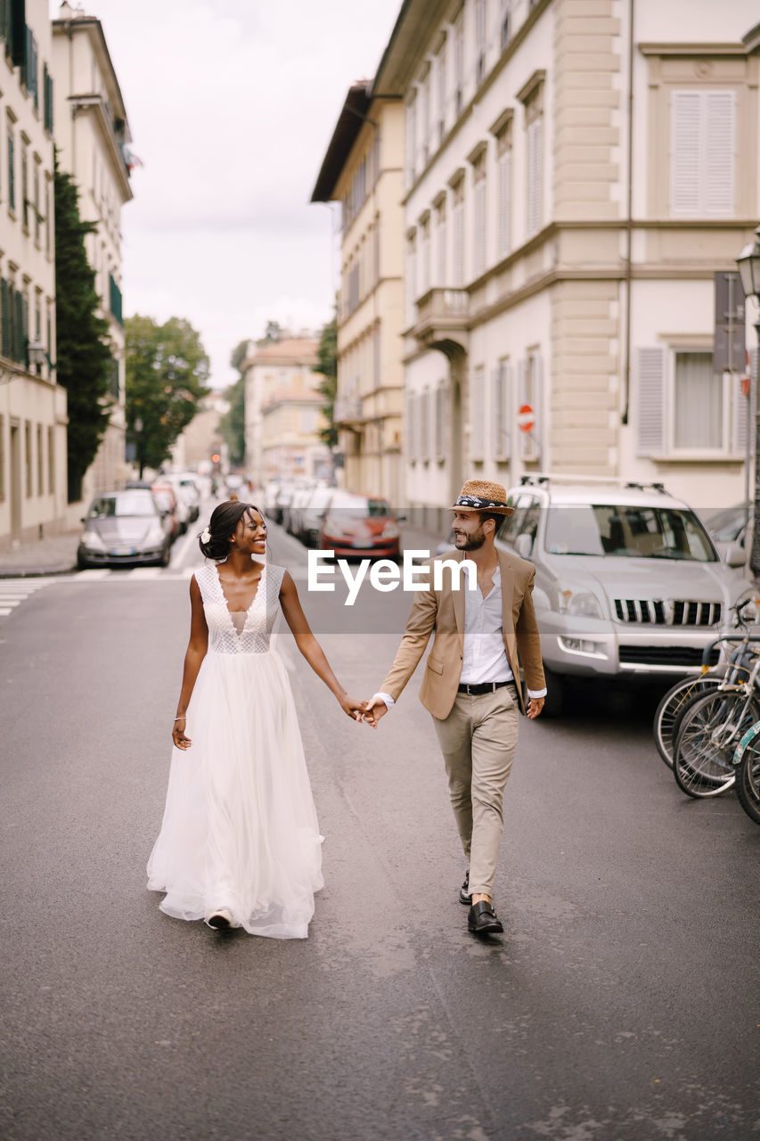 Couple holding hand walking on street