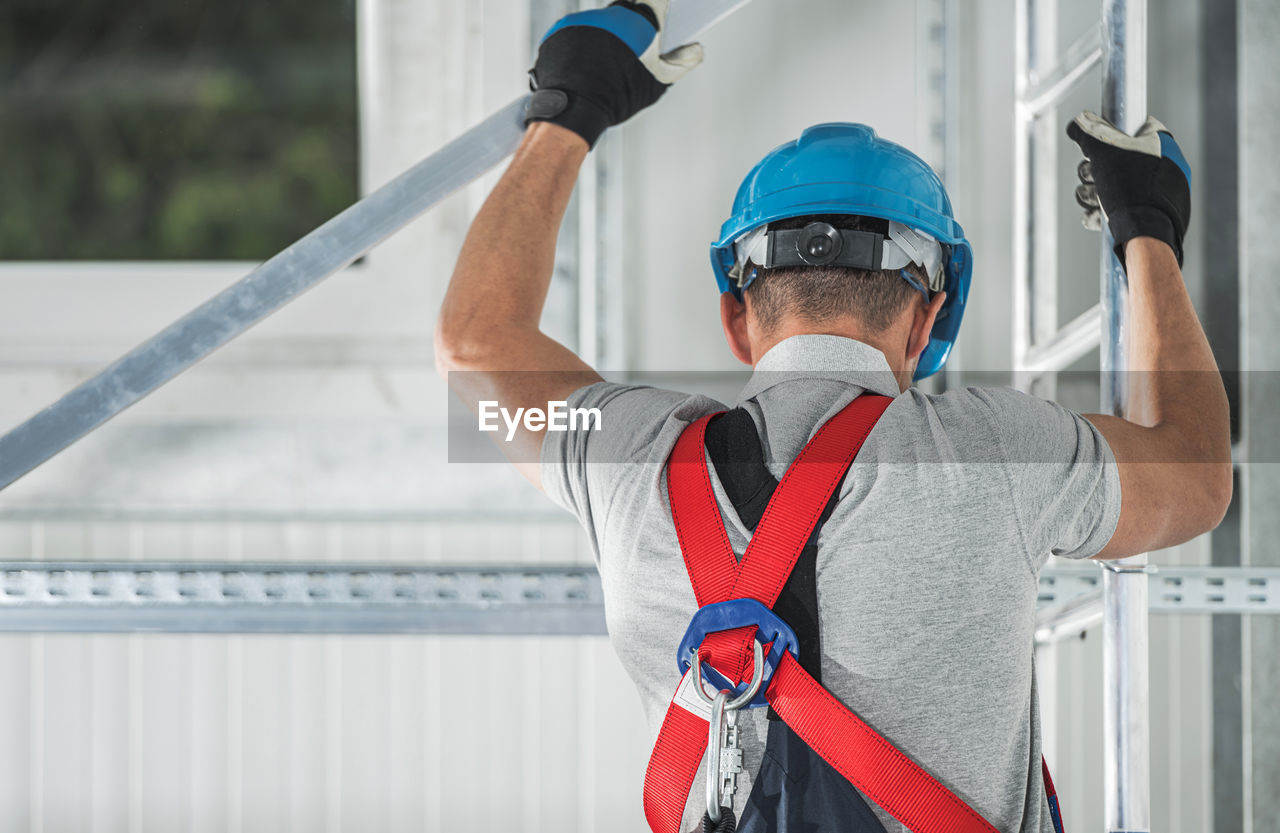 REAR VIEW OF MAN WORKING WITH UMBRELLA