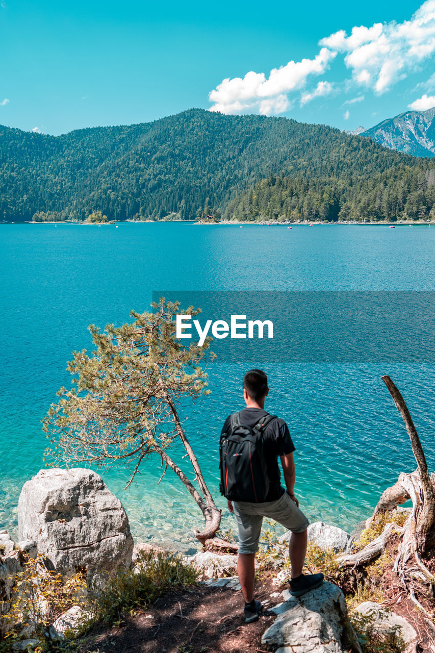 Rear view of man looking at lake against mountains