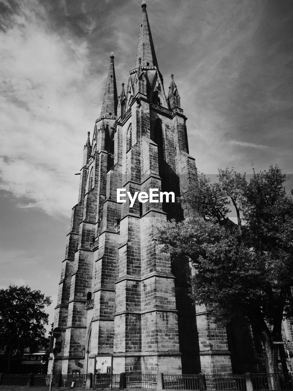 built structure, building exterior, architecture, low angle view, sky, religion, place of worship, belief, spirituality, building, tower, cloud - sky, tree, nature, plant, history, the past, travel destinations, no people, outdoors, gothic style, spire