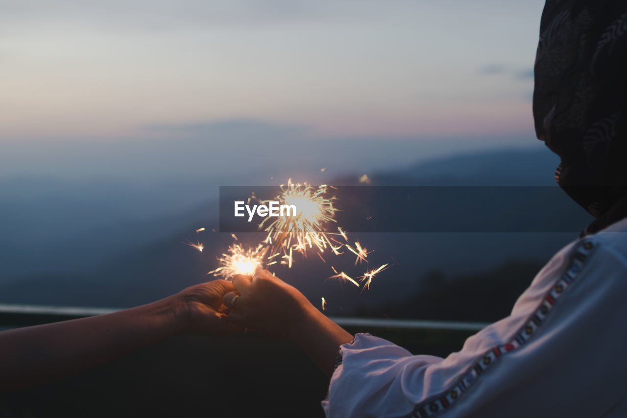 Woman With Friend Holding Sparklers Against Sky During Sunset