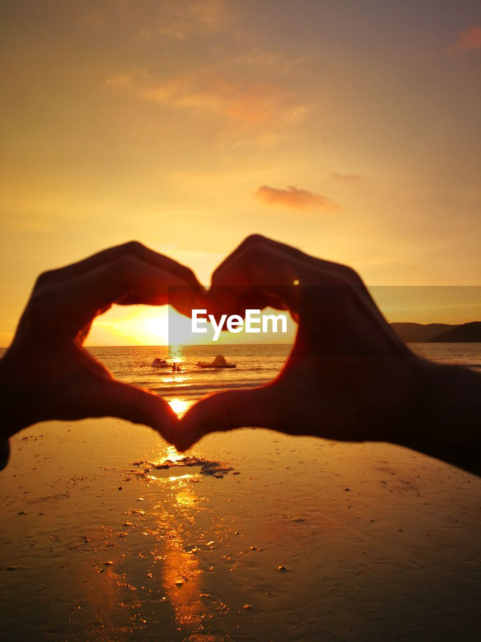 sunset, heart shape, human hand, sky, positive emotion, hand, love, human body part, orange color, sea, water, one person, emotion, making, beach, scenics - nature, body part, real people, land, sun, horizon over water, finger, couple - relationship, outdoors