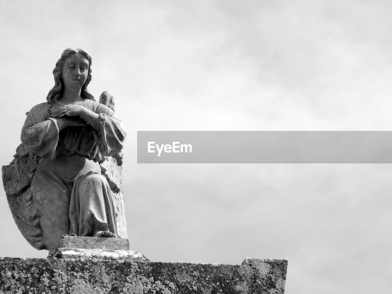 Low Angle View Of Broken Angel Statue Against Sky