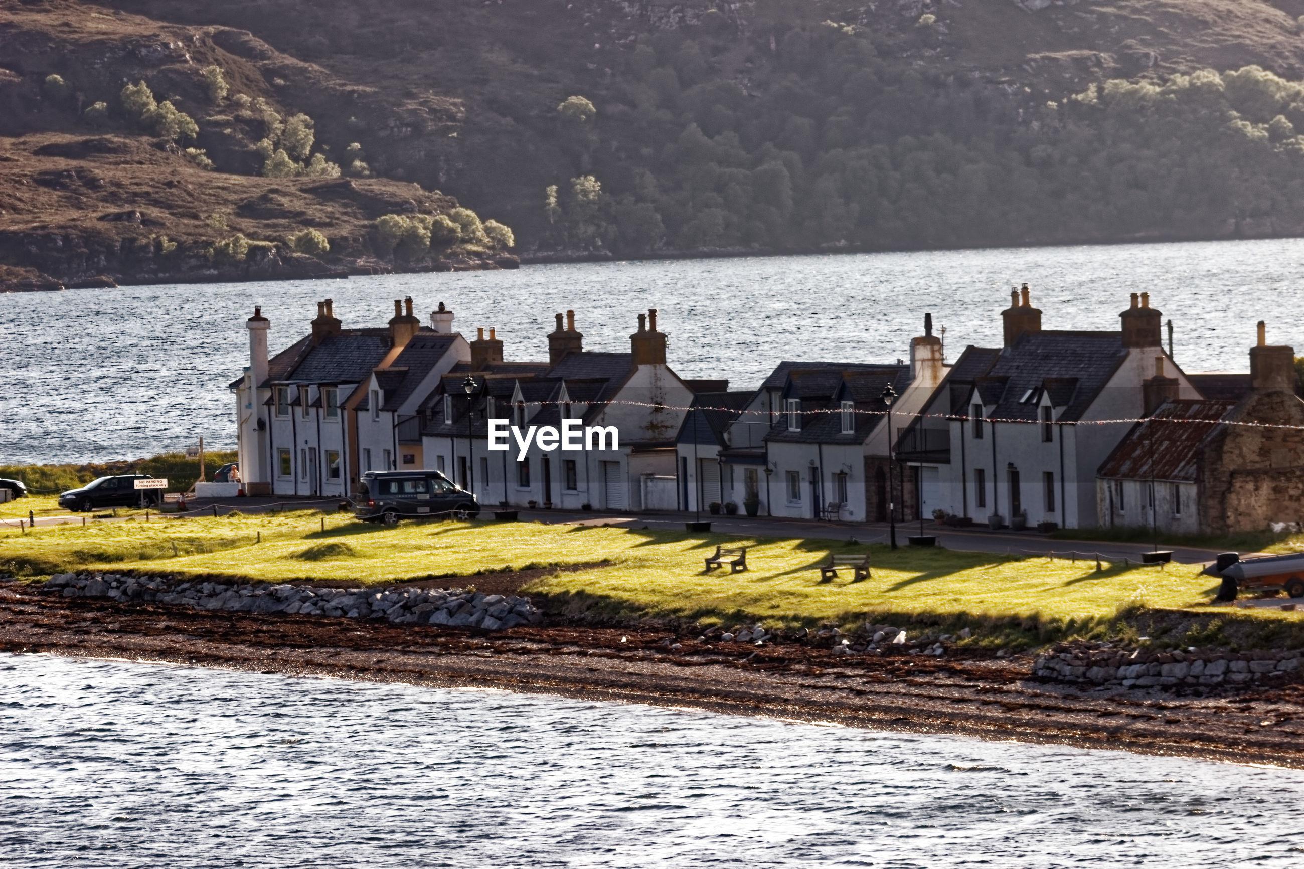 HOUSES ON BEACH BY SEA AGAINST BUILDINGS