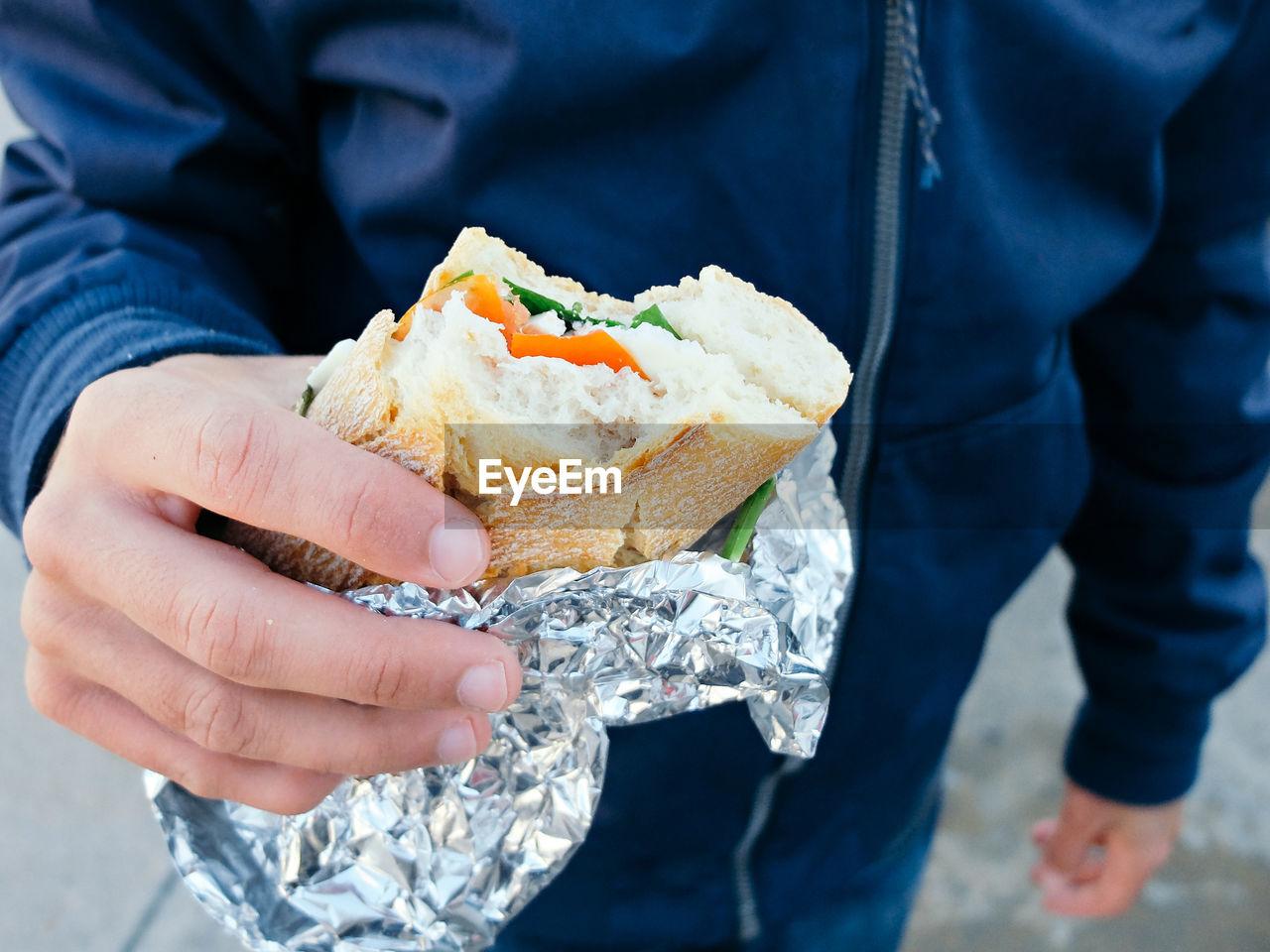 Close-Up Of Man Holding Sandwich