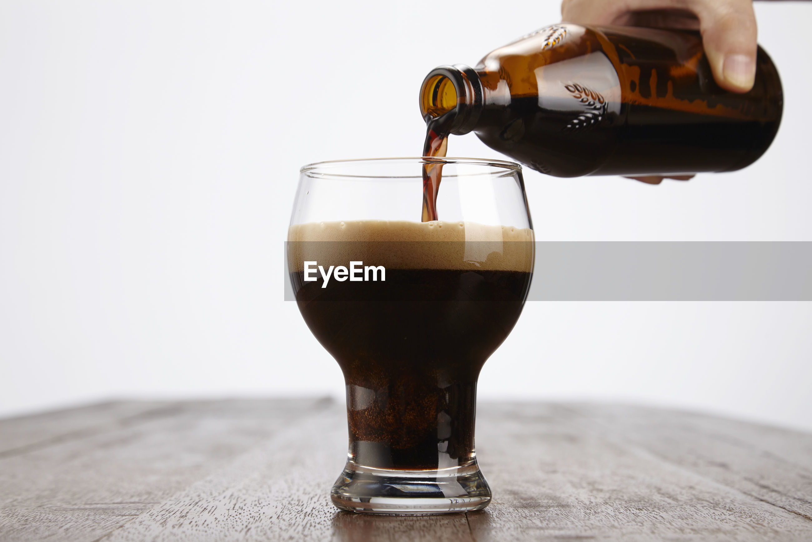 Close-up of drink pouring in glass on table against white background