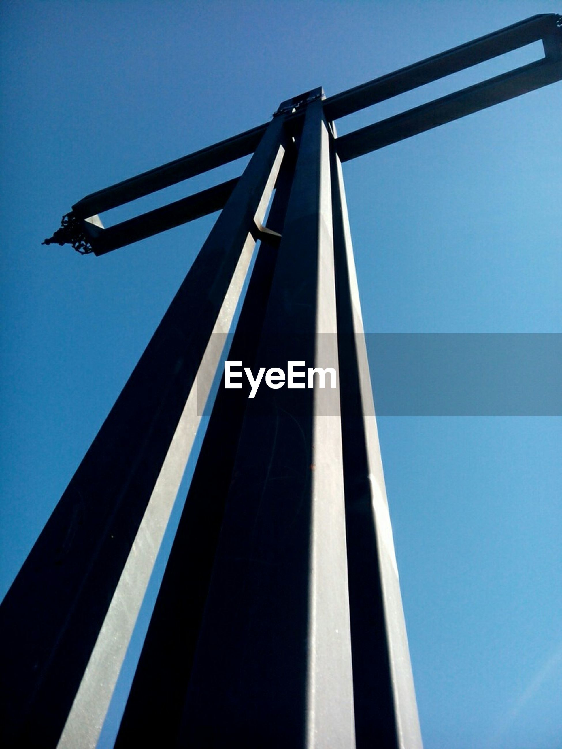 low angle view, clear sky, blue, built structure, architecture, sky, copy space, no people, day, outdoors, connection, metal, sunlight, part of, tall - high, high section, tall, technology, building exterior, pole