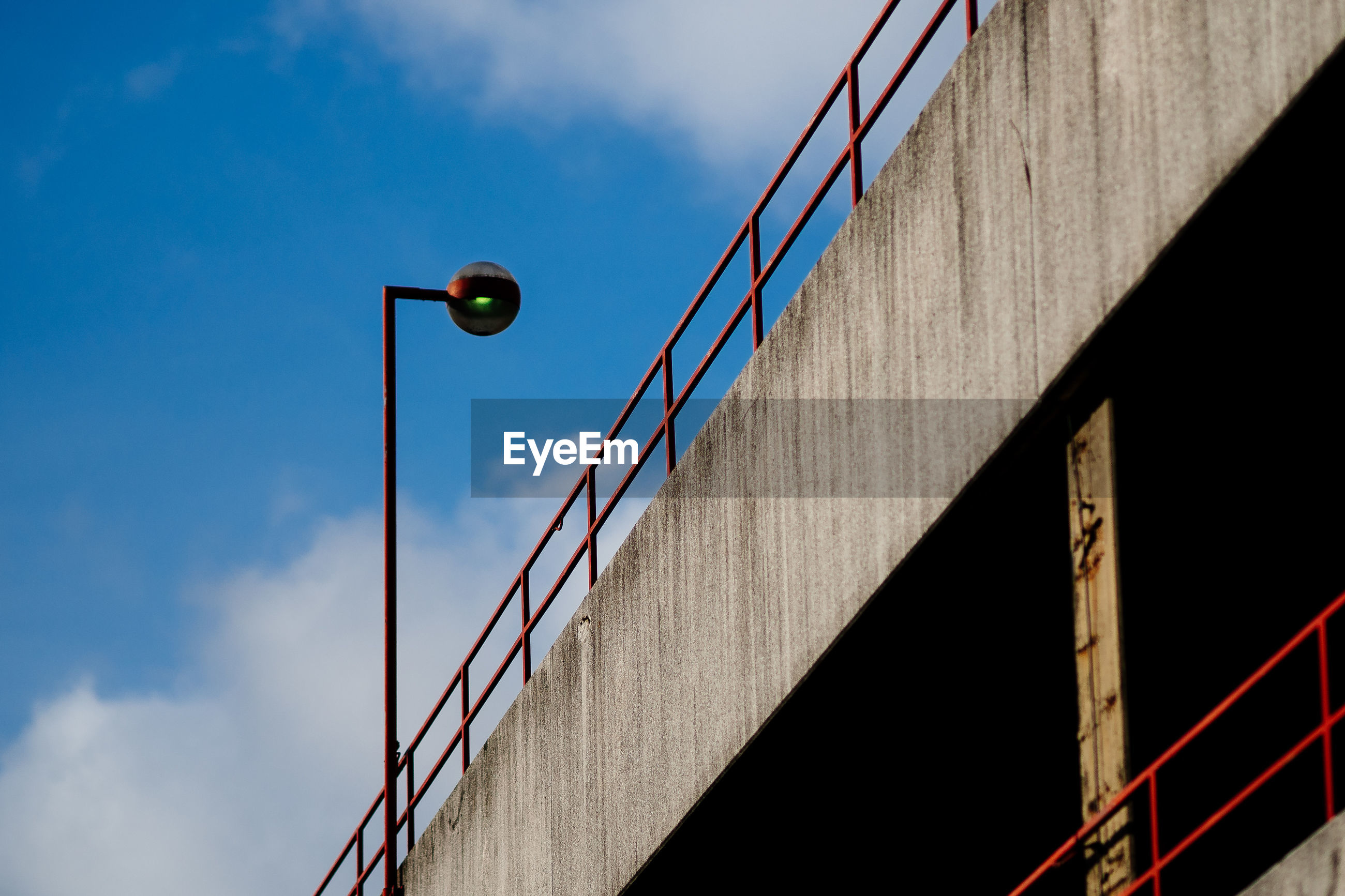 Low angle view of street light by bridge against sky