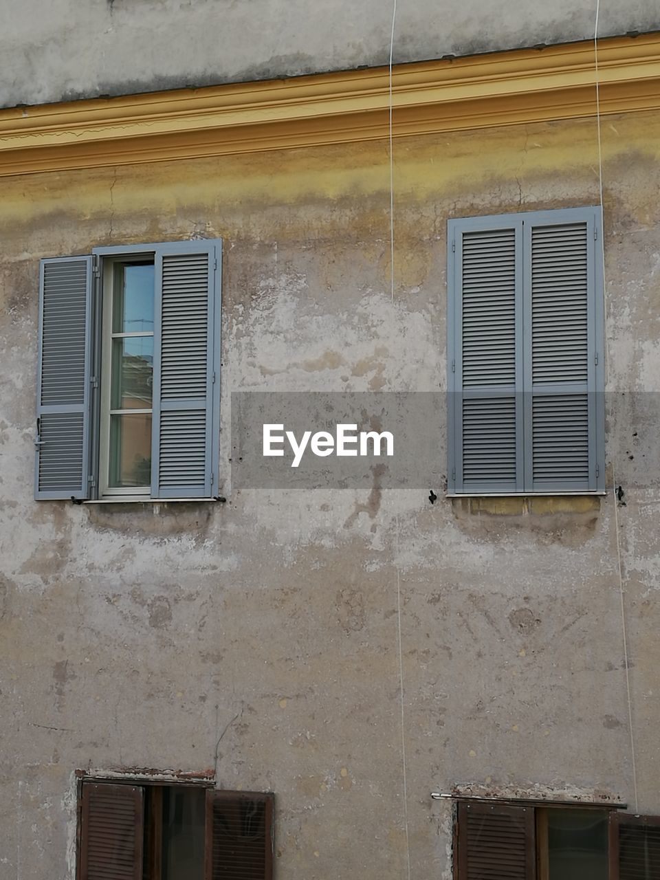 window, architecture, building, building exterior, built structure, no people, day, wall - building feature, residential district, house, low angle view, old, outdoors, shutter, wall, facade, closed, reflection, protection, nature, window frame, apartment