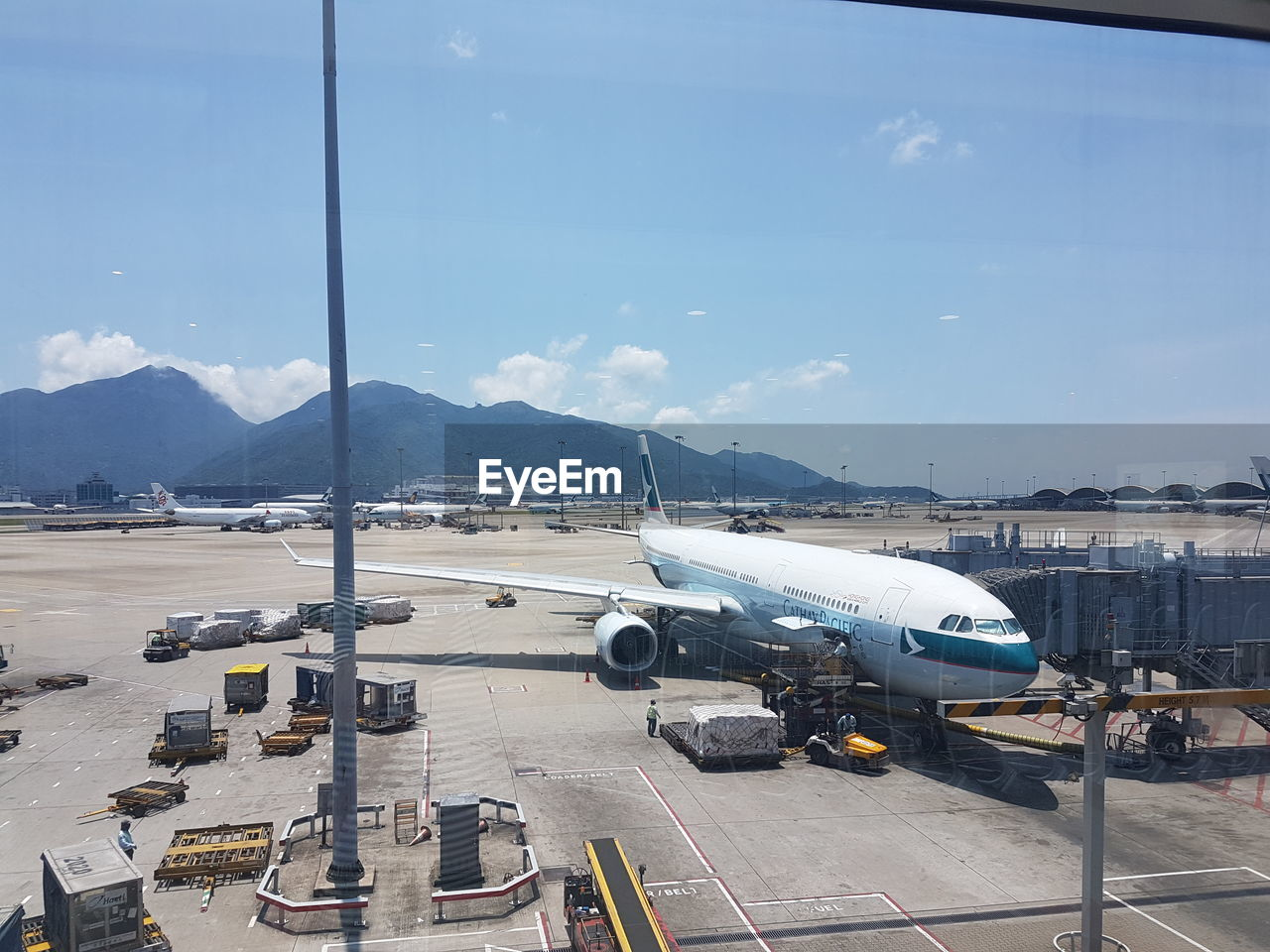transportation, airplane, mode of transport, passenger boarding bridge, airport, day, airport runway, sky, no people, mountain, outdoors, air vehicle