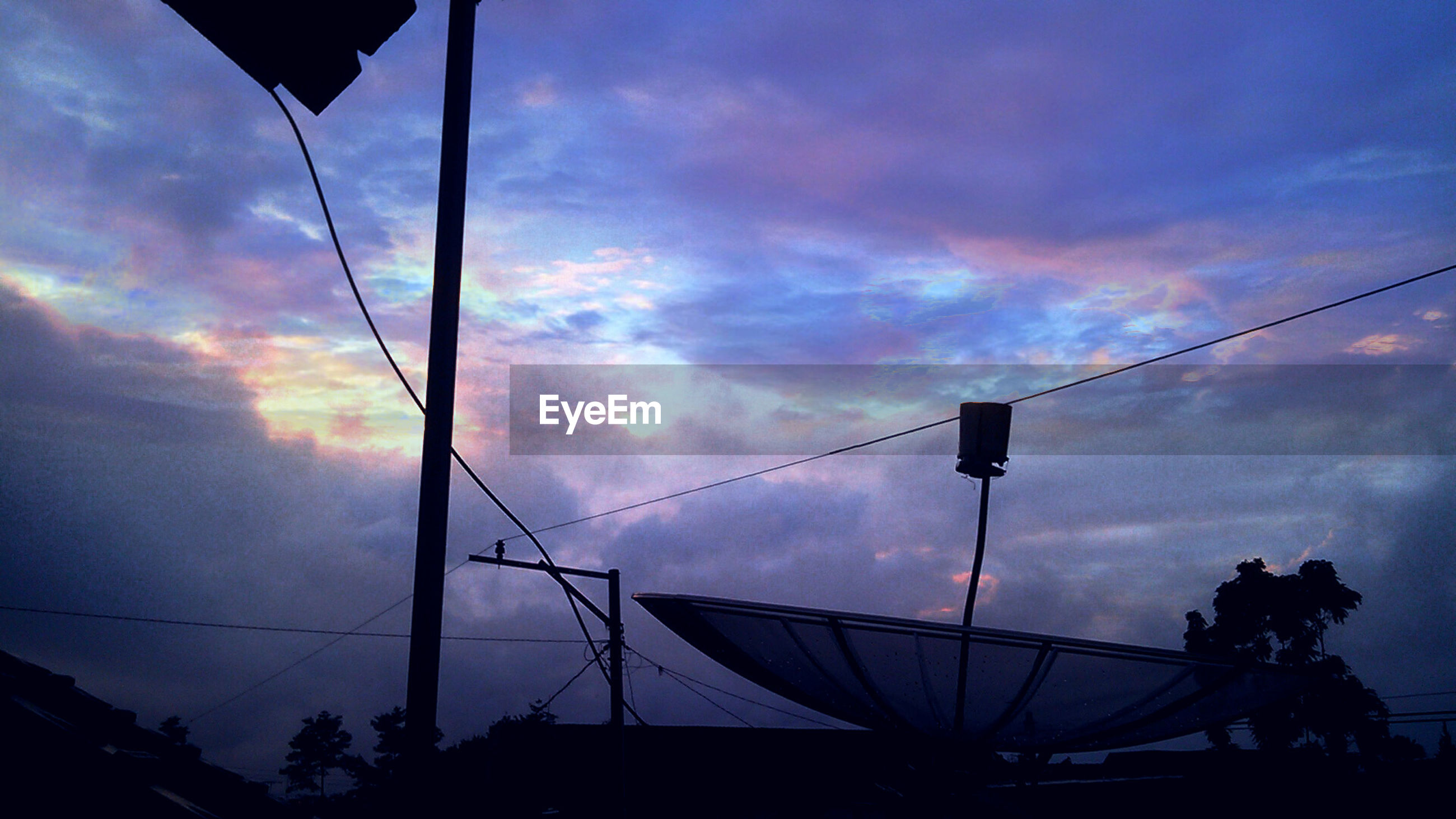 Satellite dish against cloudy sky during sunset