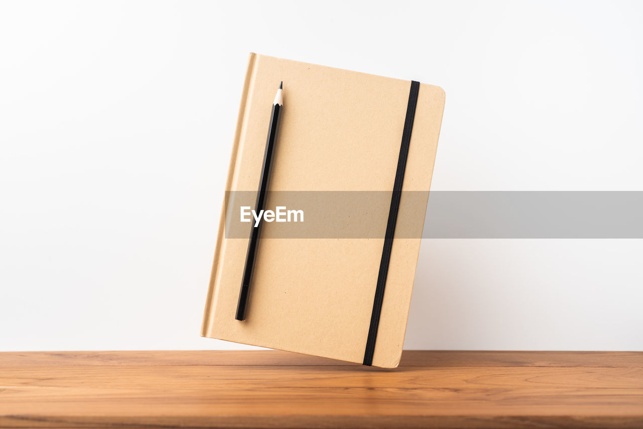 indoors, studio shot, white background, wood - material, copy space, no people, still life, paper, table, blank, wood, single object, close-up, simplicity, office, brown, high angle view, education, cut out, pencil