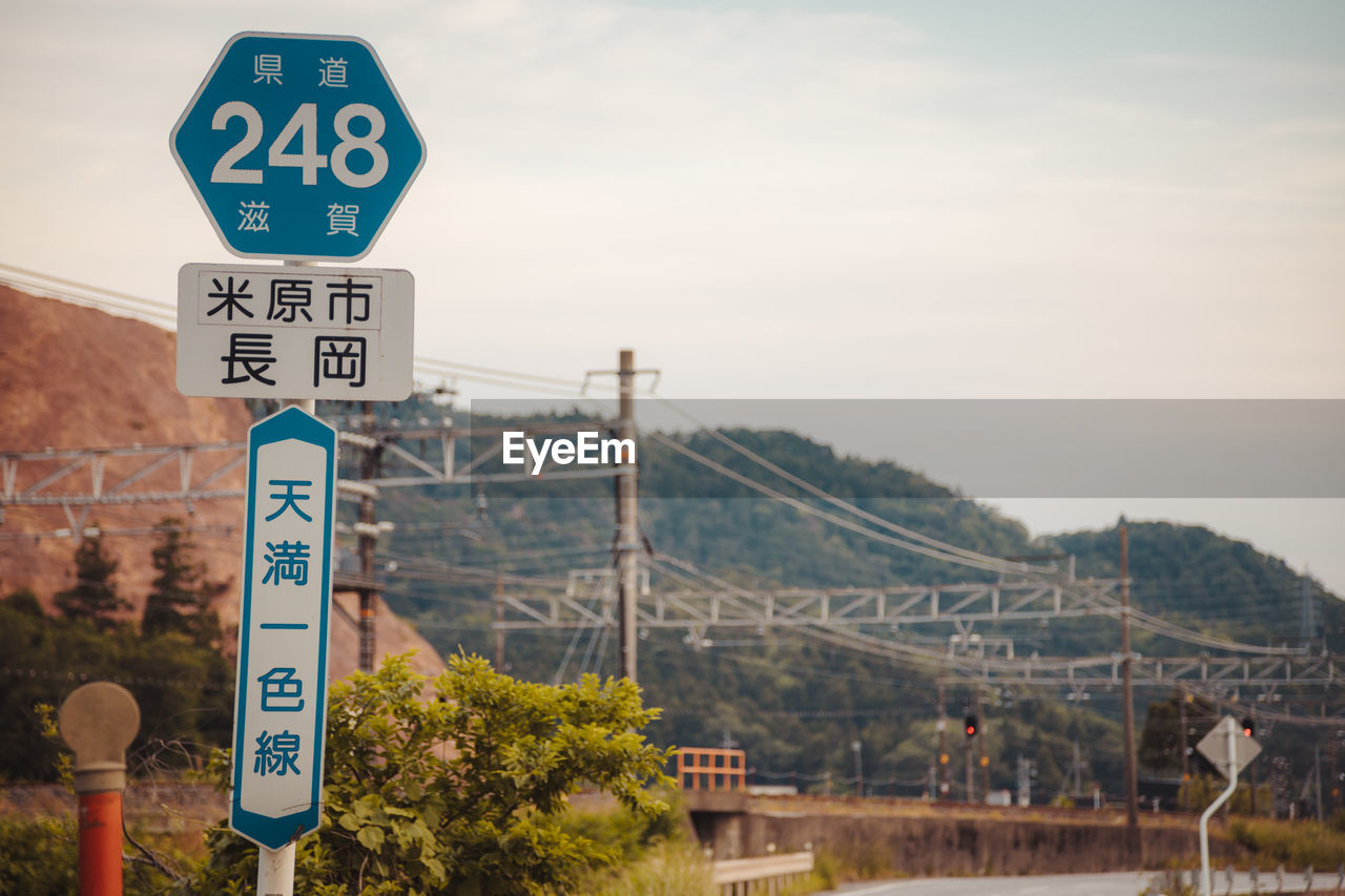 communication, sign, text, guidance, sky, focus on foreground, nature, day, road sign, information, built structure, no people, representation, western script, information sign, human representation, architecture, number, outdoors, pedestrian crossing sign