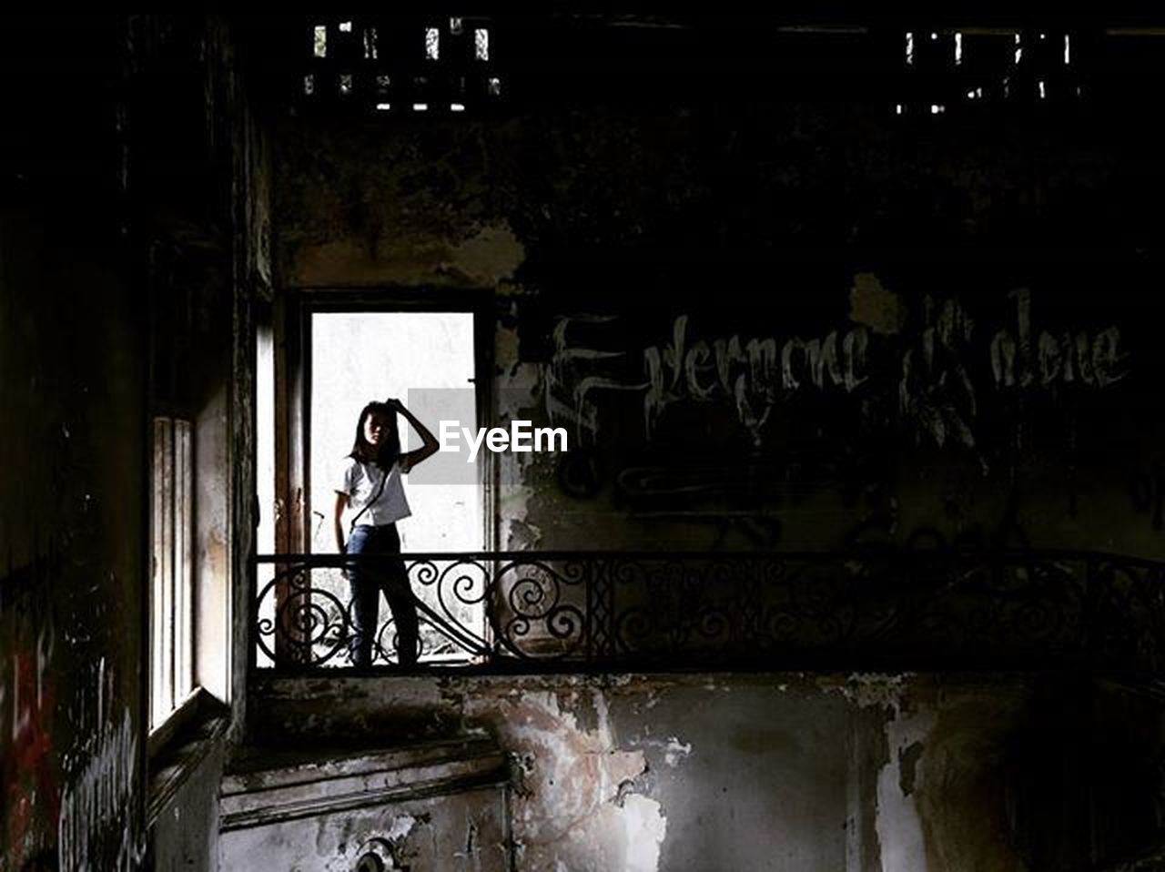 graffiti, full length, one person, one woman only, built structure, adult, only women, adults only, standing, architecture, people, street art, portrait, day, women, young adult, looking at camera, doorway, young women, indoors, building exterior, real people, one young woman only
