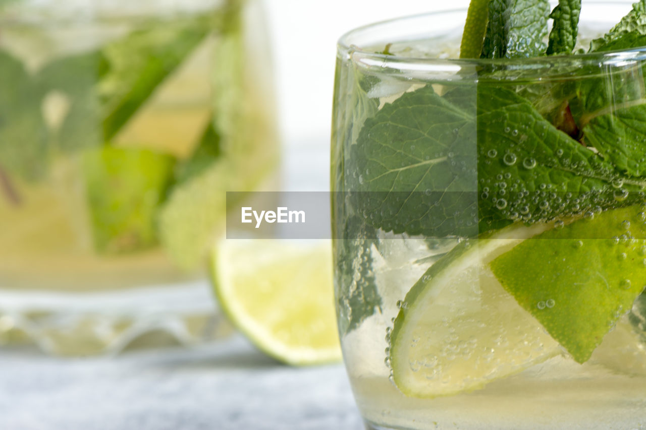 Close-up of mojito on table against white background