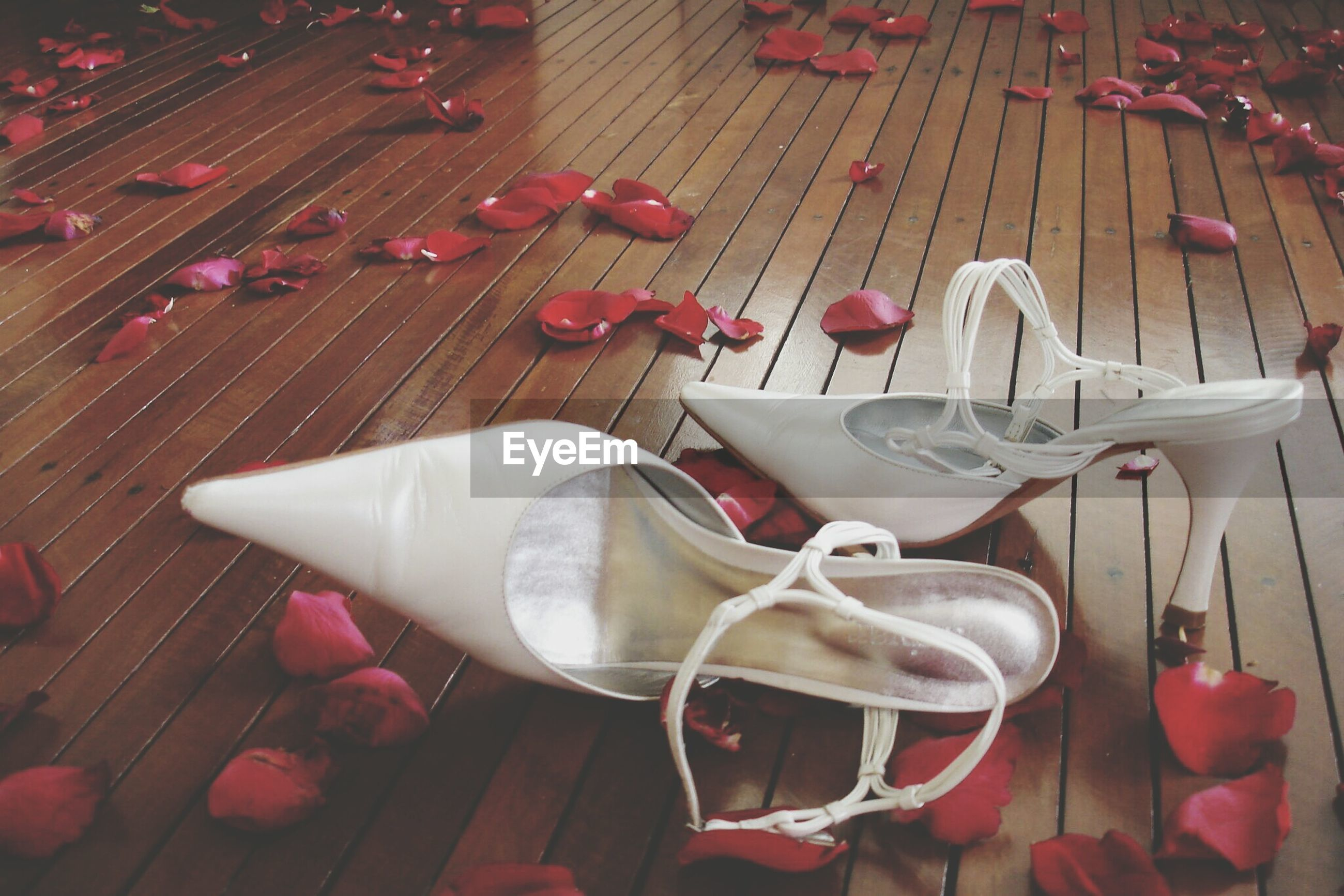 High heels and rose petals on wooden floor