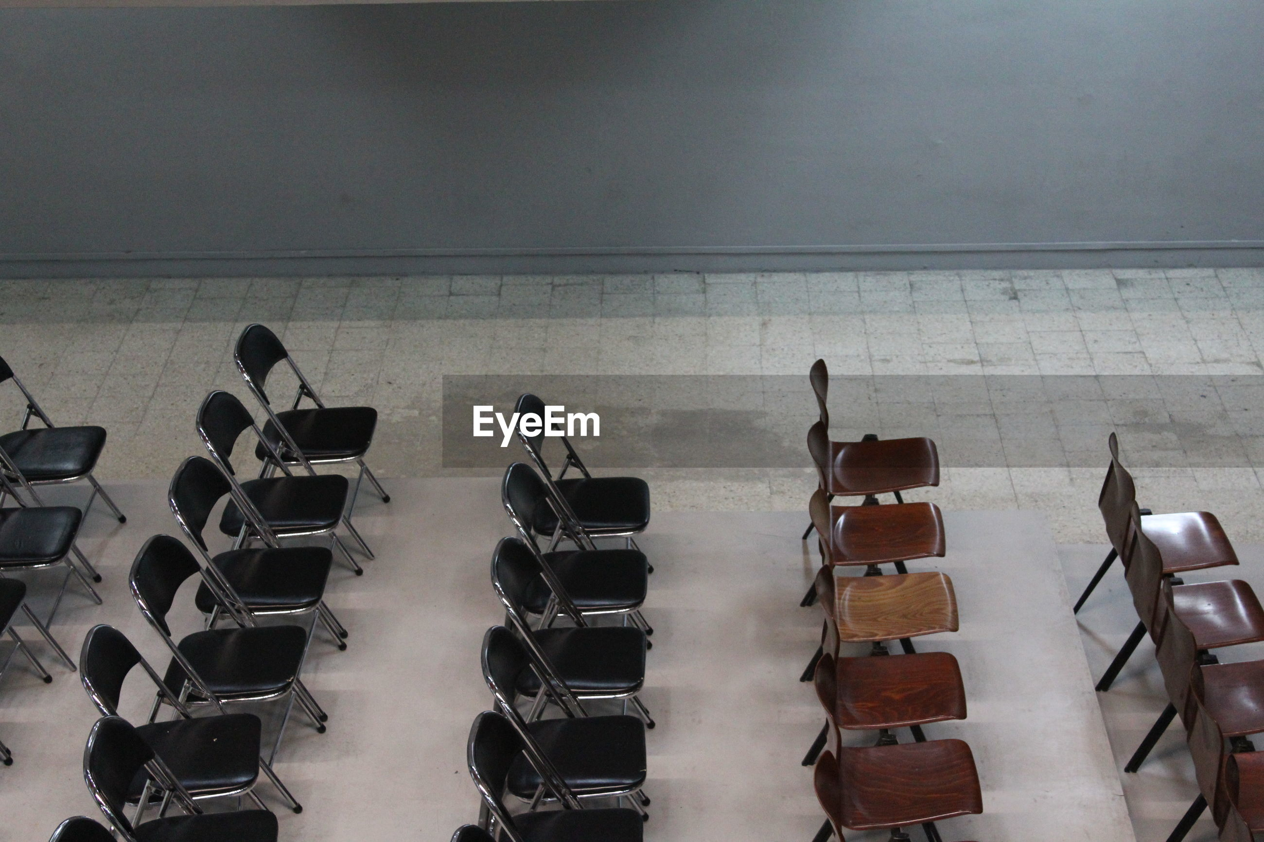 High angle view of chairs arranged by wall