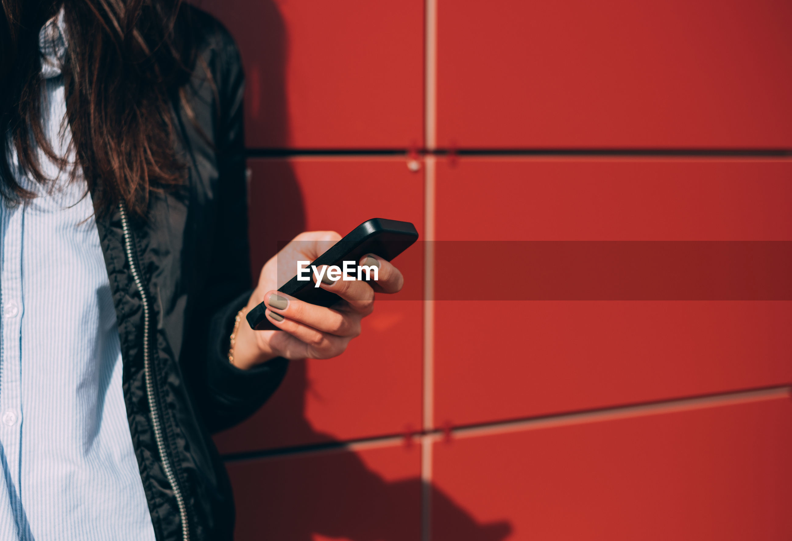 Midsection of woman using mobile phone against red wall