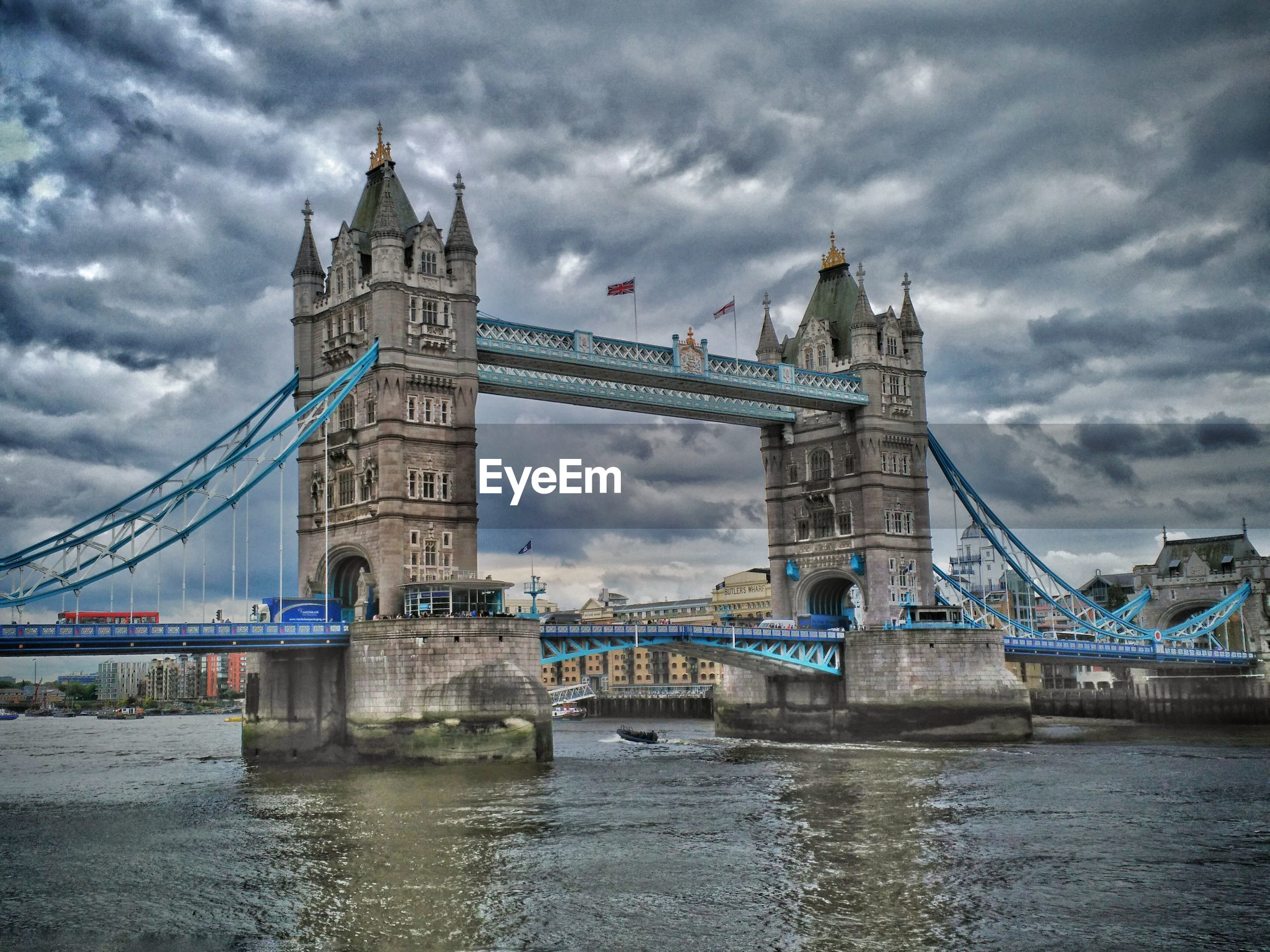 architecture, built structure, sky, connection, cloud - sky, bridge - man made structure, water, cloudy, river, waterfront, cloud, engineering, bridge, city, travel destinations, overcast, weather, outdoors, capital cities, tower bridge, no people, tourism, day, rippled, city life, nature, culture