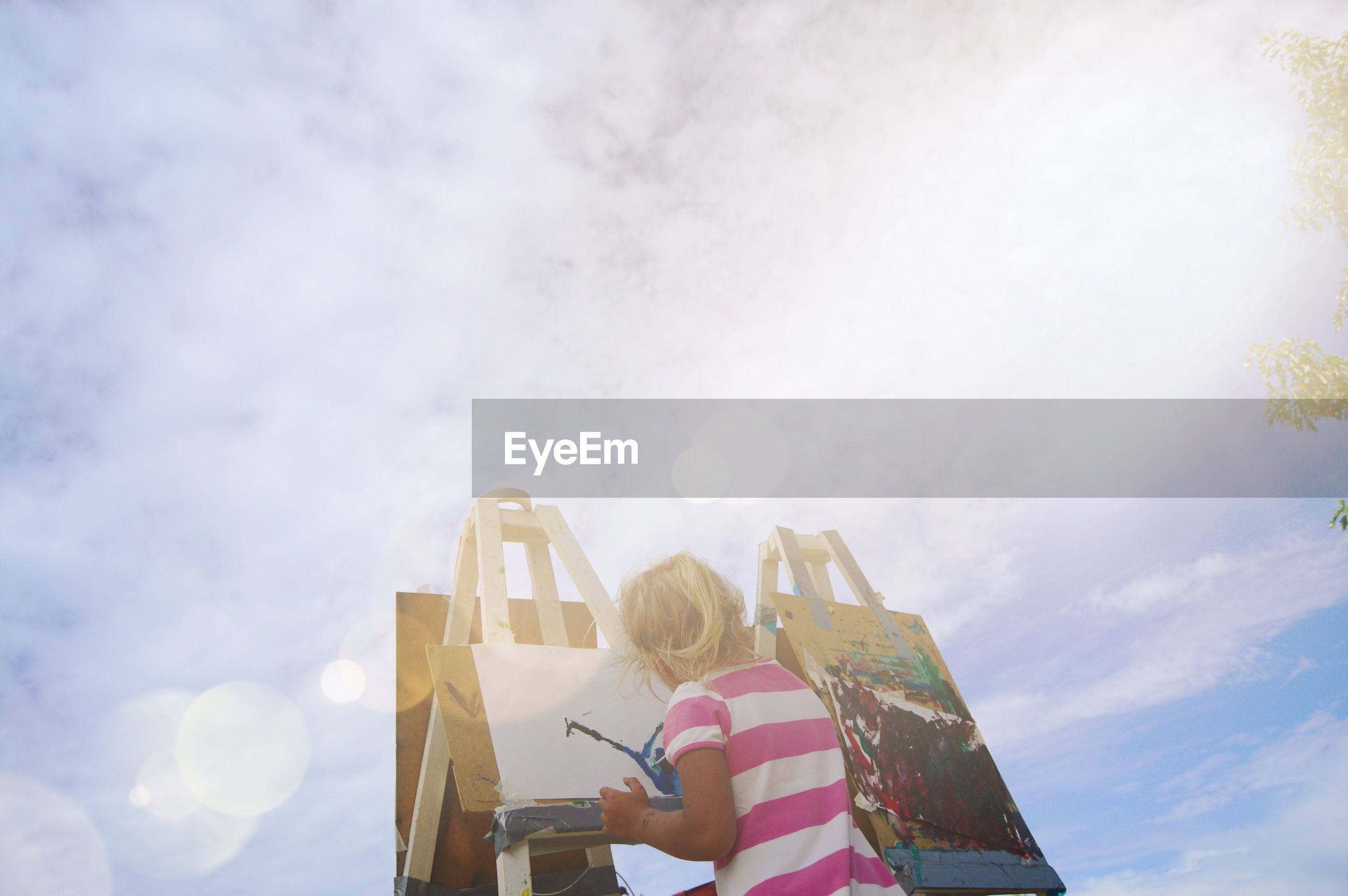 Rear view of girl making painting on canvas against cloudy sky