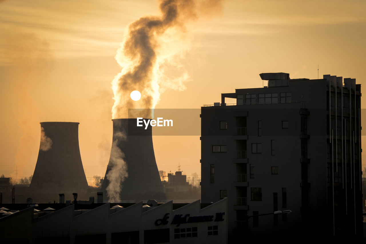 building exterior, smoke - physical structure, built structure, architecture, sky, pollution, environmental issues, smoke stack, factory, air pollution, emitting, industry, environment, nature, sunset, no people, chimney, orange color, city, outdoors, fumes, atmospheric