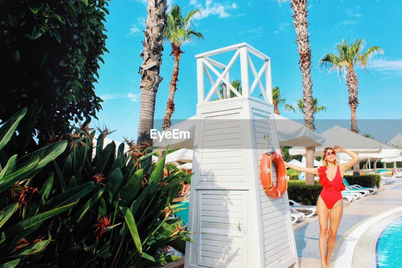 Woman standing by lifeguard hut at poolside