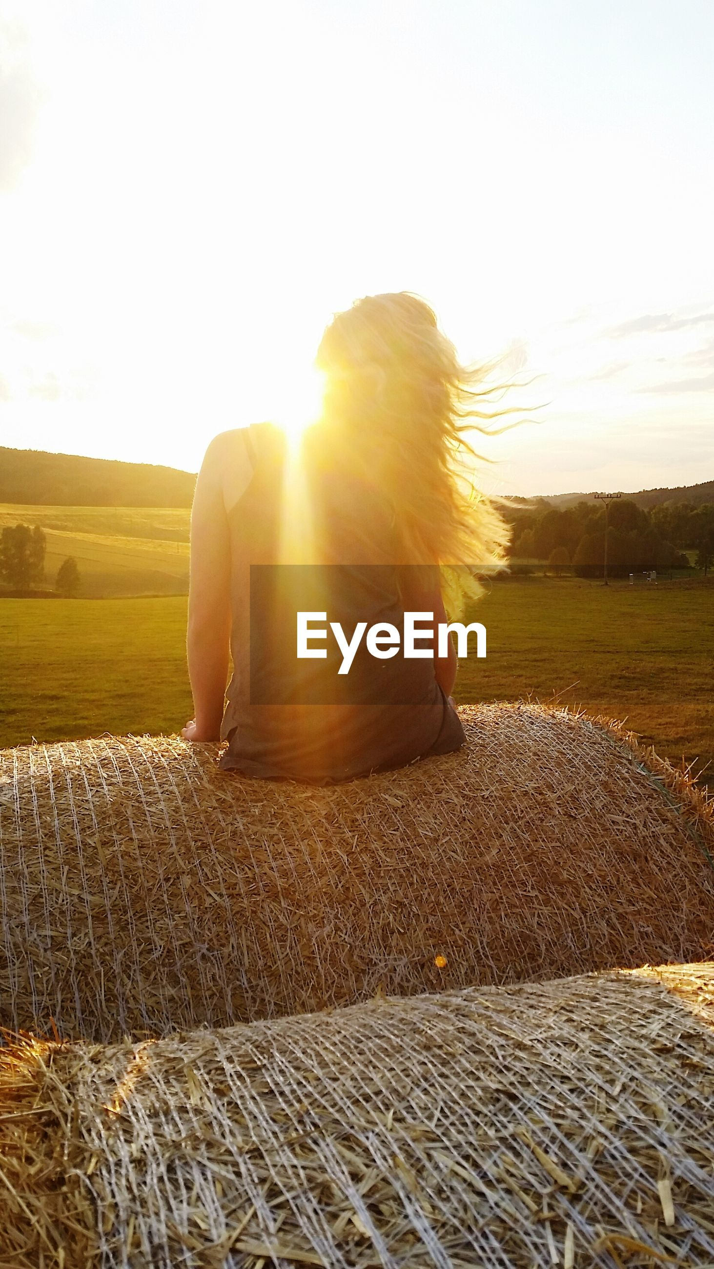 sun, lifestyles, leisure activity, sunset, sunlight, full length, sunbeam, field, landscape, rear view, sky, lens flare, casual clothing, standing, tranquility, nature, tranquil scene, person