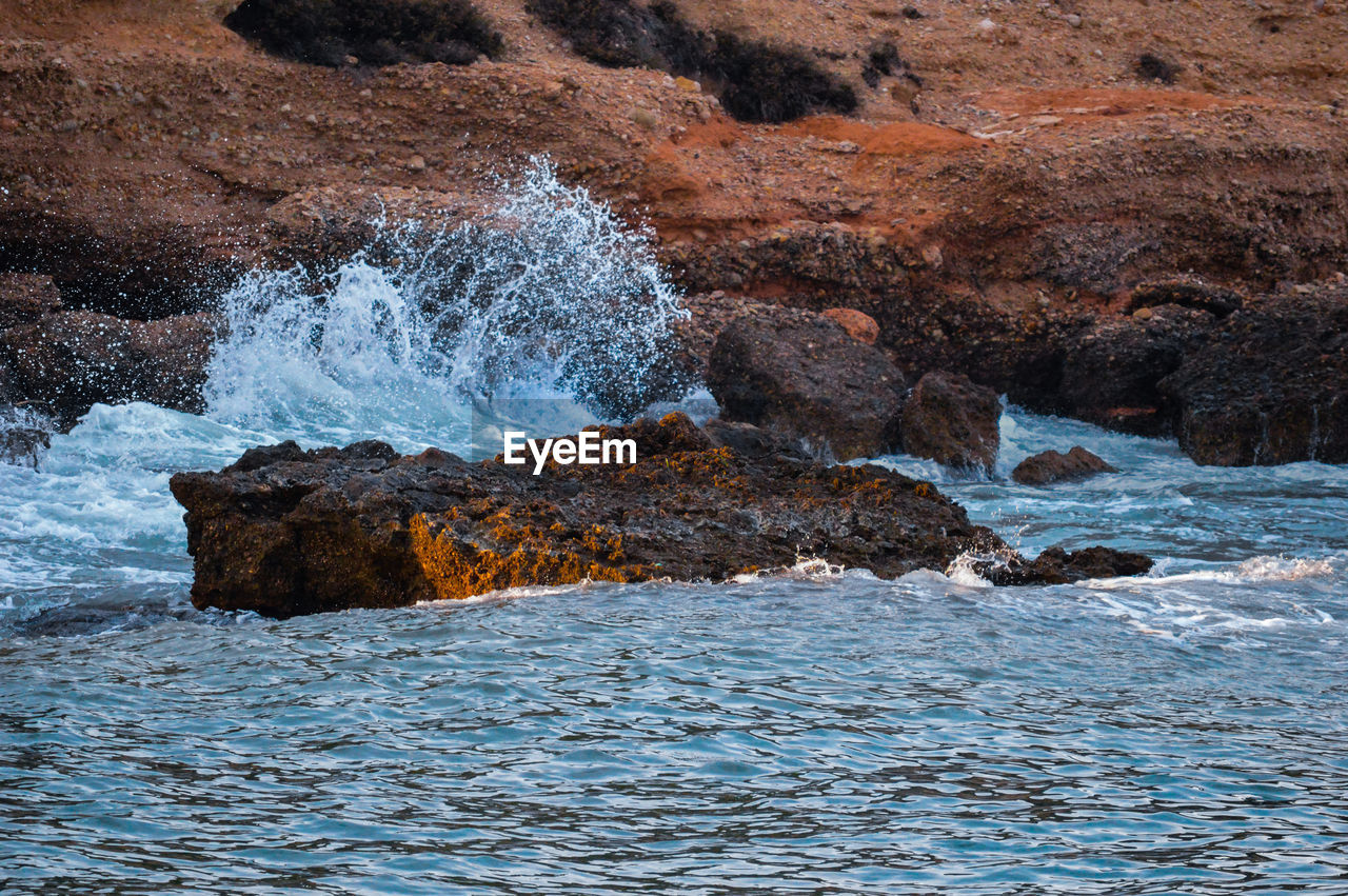 water, sea, rock, beauty in nature, motion, rock - object, solid, wave, waterfront, nature, power in nature, scenics - nature, rock formation, power, aquatic sport, sport, splashing, surfing, outdoors, breaking, flowing water, hitting