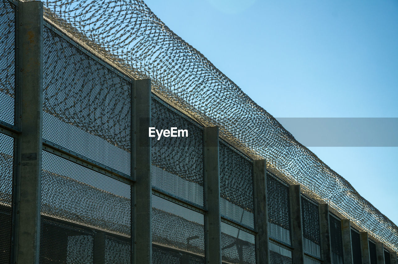 Low Angle View Of A Security Fence Against Sky