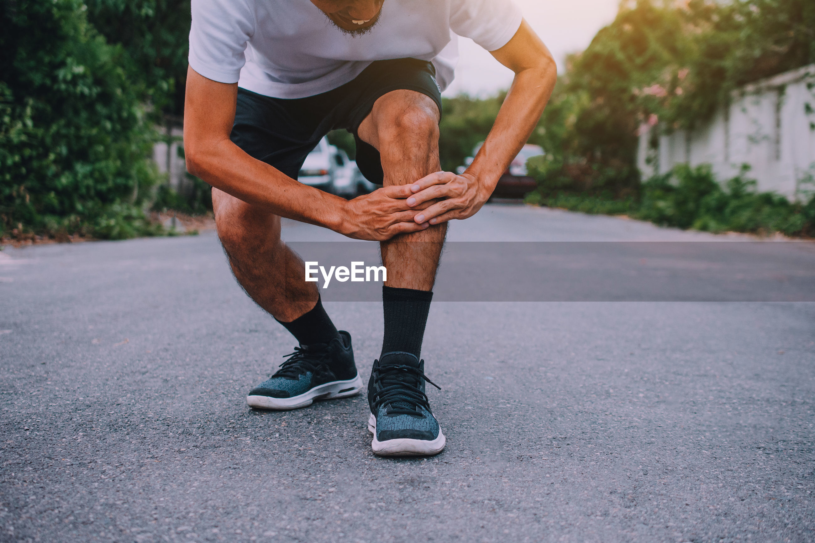 Low section of athlete with knee pain on road