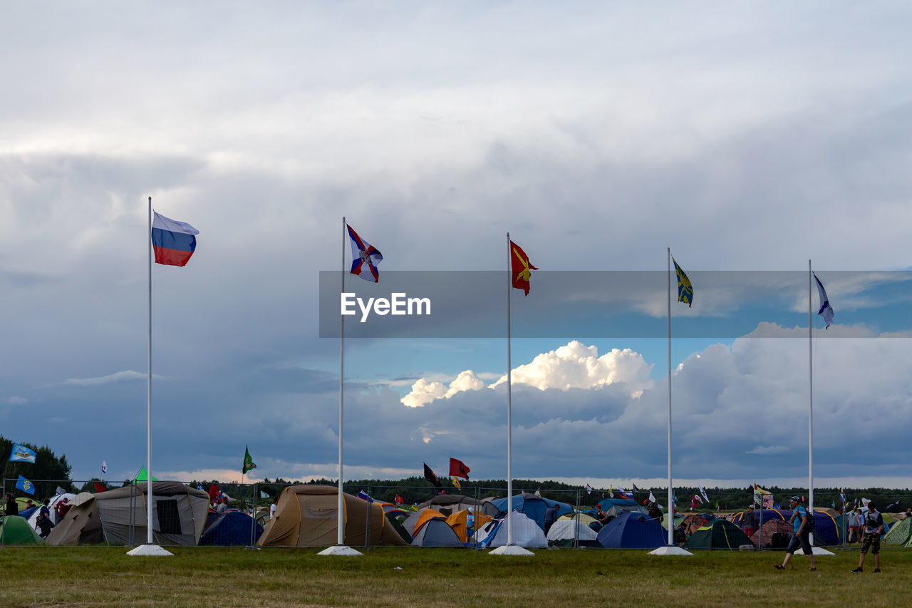 cloud - sky, flag, sky, patriotism, nature, real people, crowd, people, group of people, pole, environment, day, pride, emotion, wind, land, men, outdoors, independence