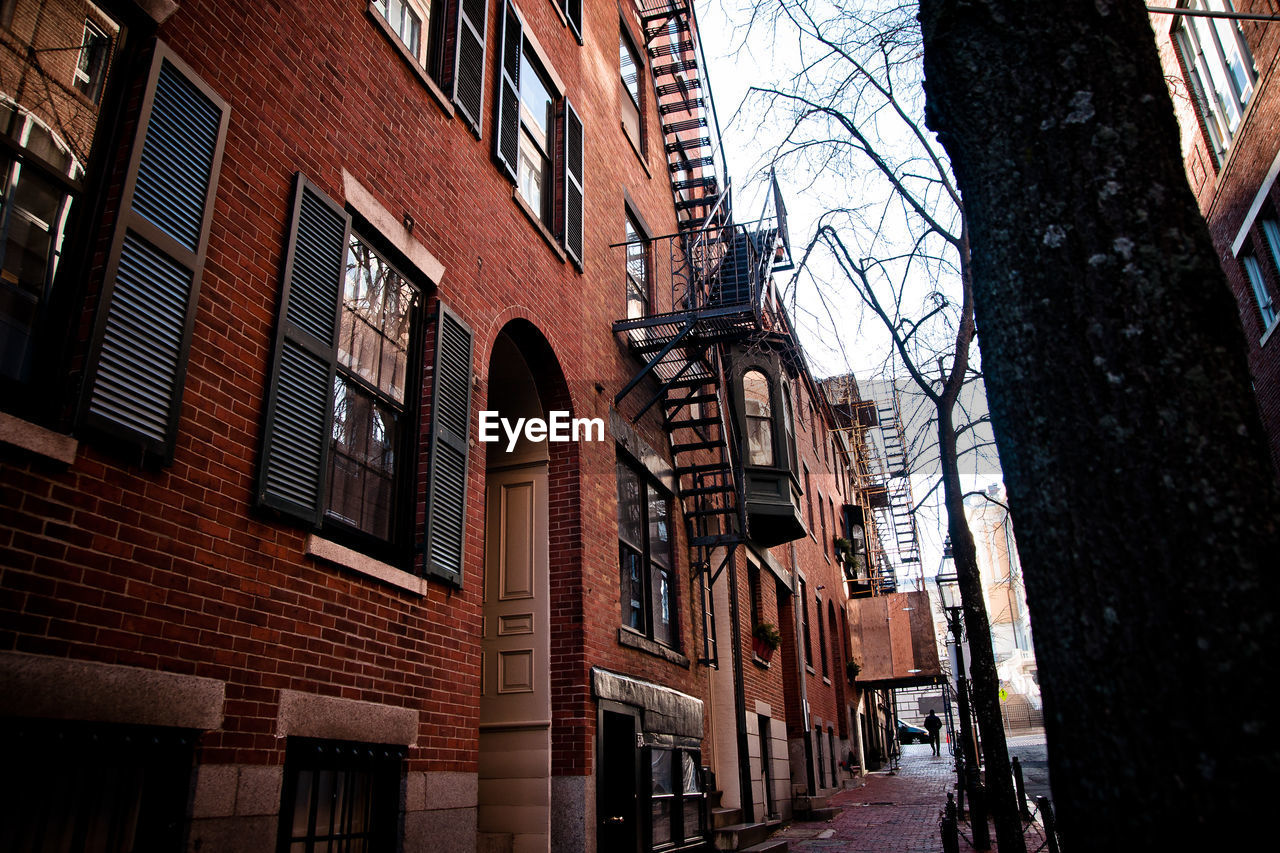 building exterior, built structure, architecture, window, low angle view, city, building, day, wall, brick, bare tree, outdoors, no people, nature, brick wall, residential district, tree, sky, arch, town, alley, row house