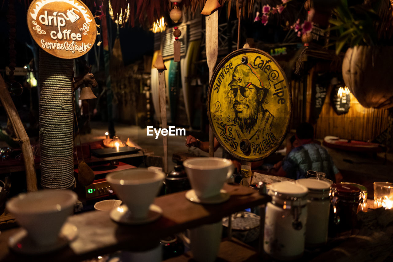lighting equipment, no people, illuminated, large group of objects, cup, indoors, hanging, business, close-up, script, selective focus, market, text, drink, non-western script, choice, mug, variation, retail, food and drink, antique, tea cup, electric lamp