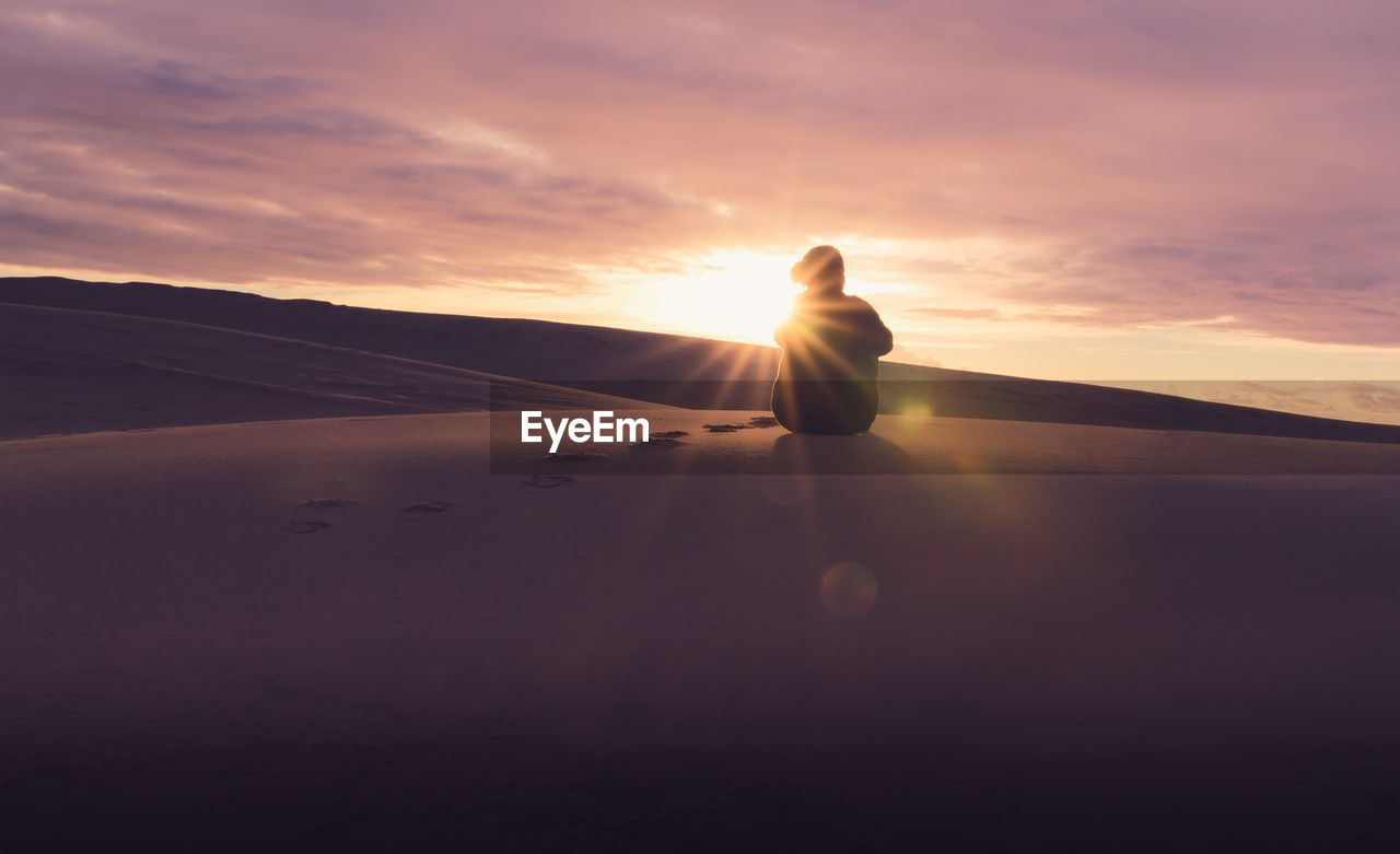 Man On Sand Dune Against Sky During Sunset