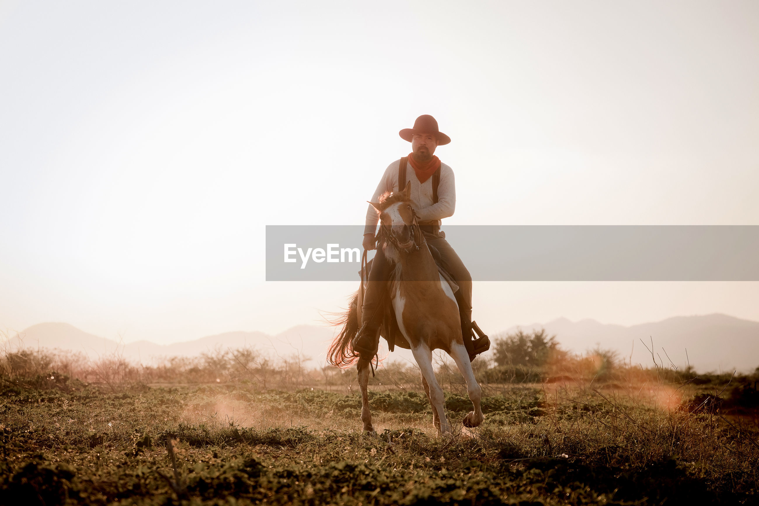 Silhouette cowboy riding a horse carrying a gun under beautiful sunset