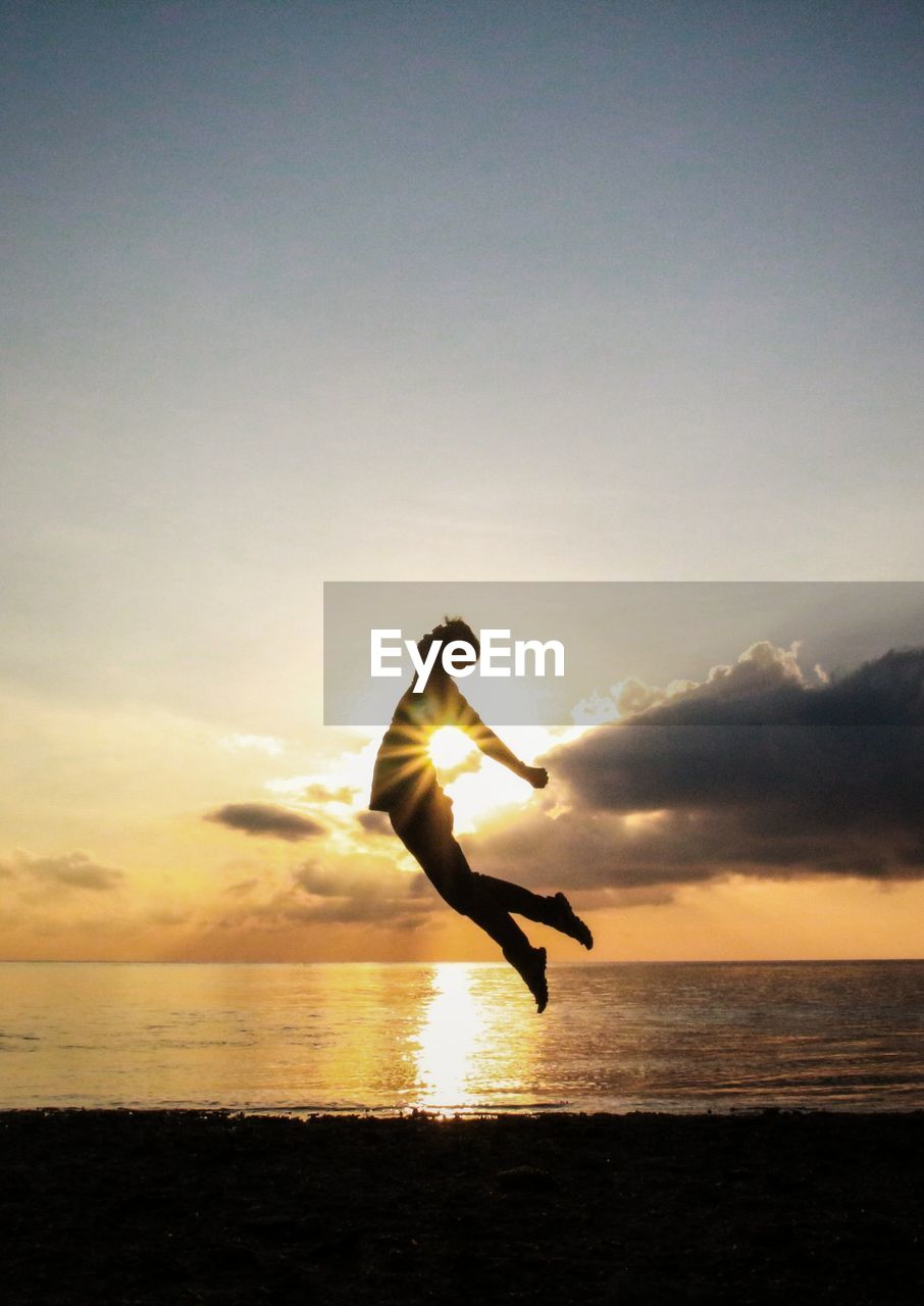 Silhouette Man Jumping On Beach Against Sky During Sunset