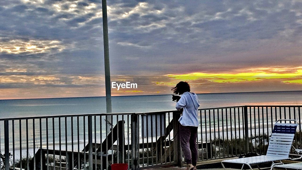 sky, sunset, cloud - sky, sea, standing, water, one person, nature, real people, railing, horizon over water, scenics, outdoors, beauty in nature, leisure activity, lifestyles, nautical vessel, men, full length, fishing pole, day, people
