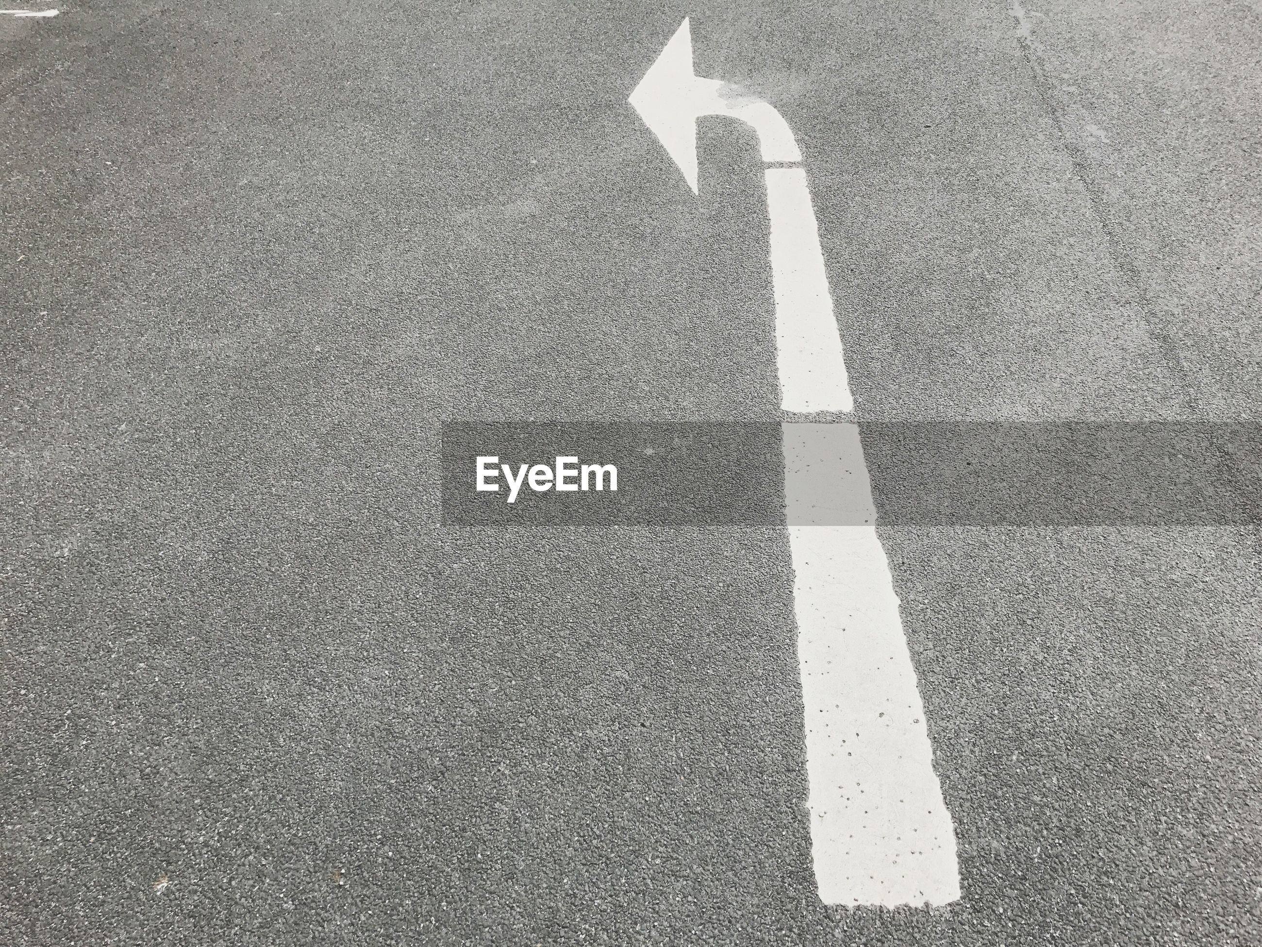 High angle view of arrow symbol on asphalt road