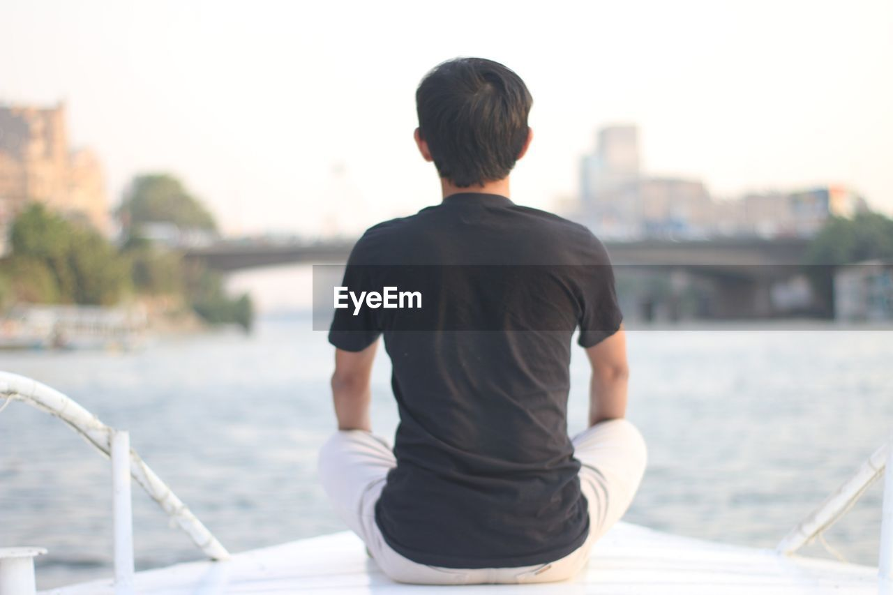 Rear View Of Man Sitting On Boat Against Sky