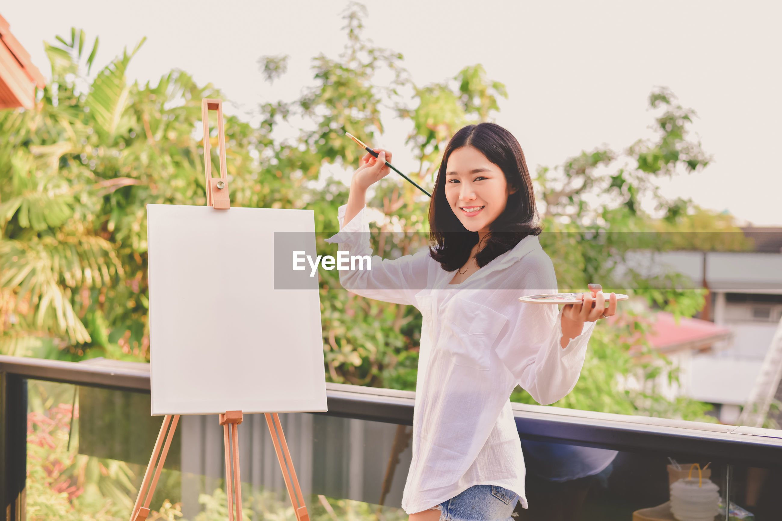Portrait of smiling woman standing by canvas against sky