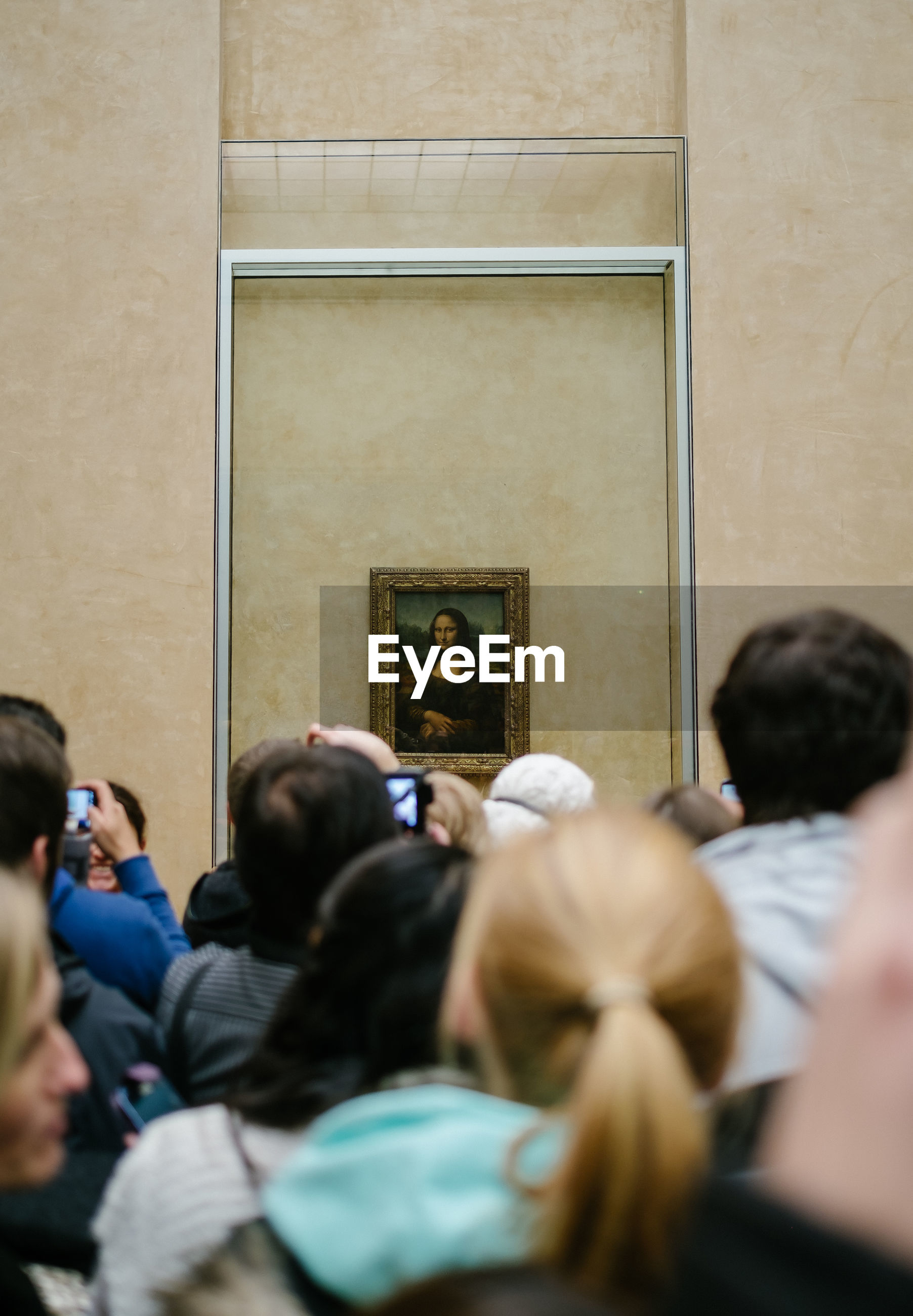 Rear view of people watching at mona lisa painting