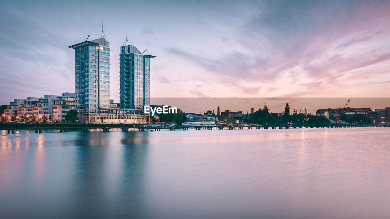 Twintowers Berlin By Spree River Against Sky During Sunset