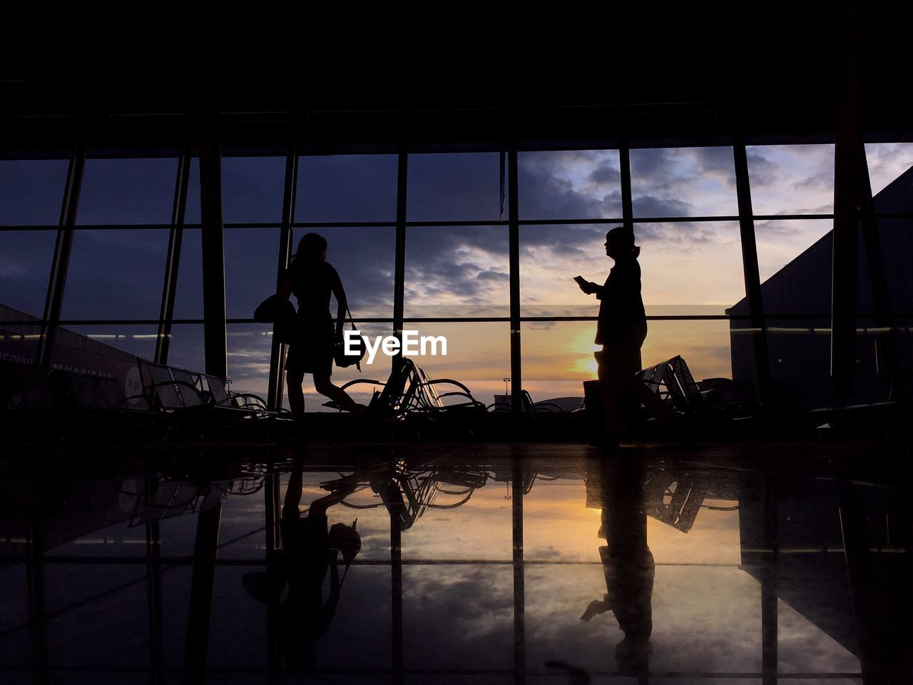 Silhouette women at airport waiting room