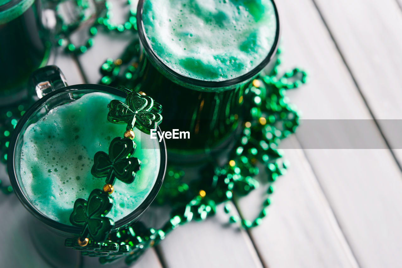 High Angle View Of Drinks With Necklace On Table