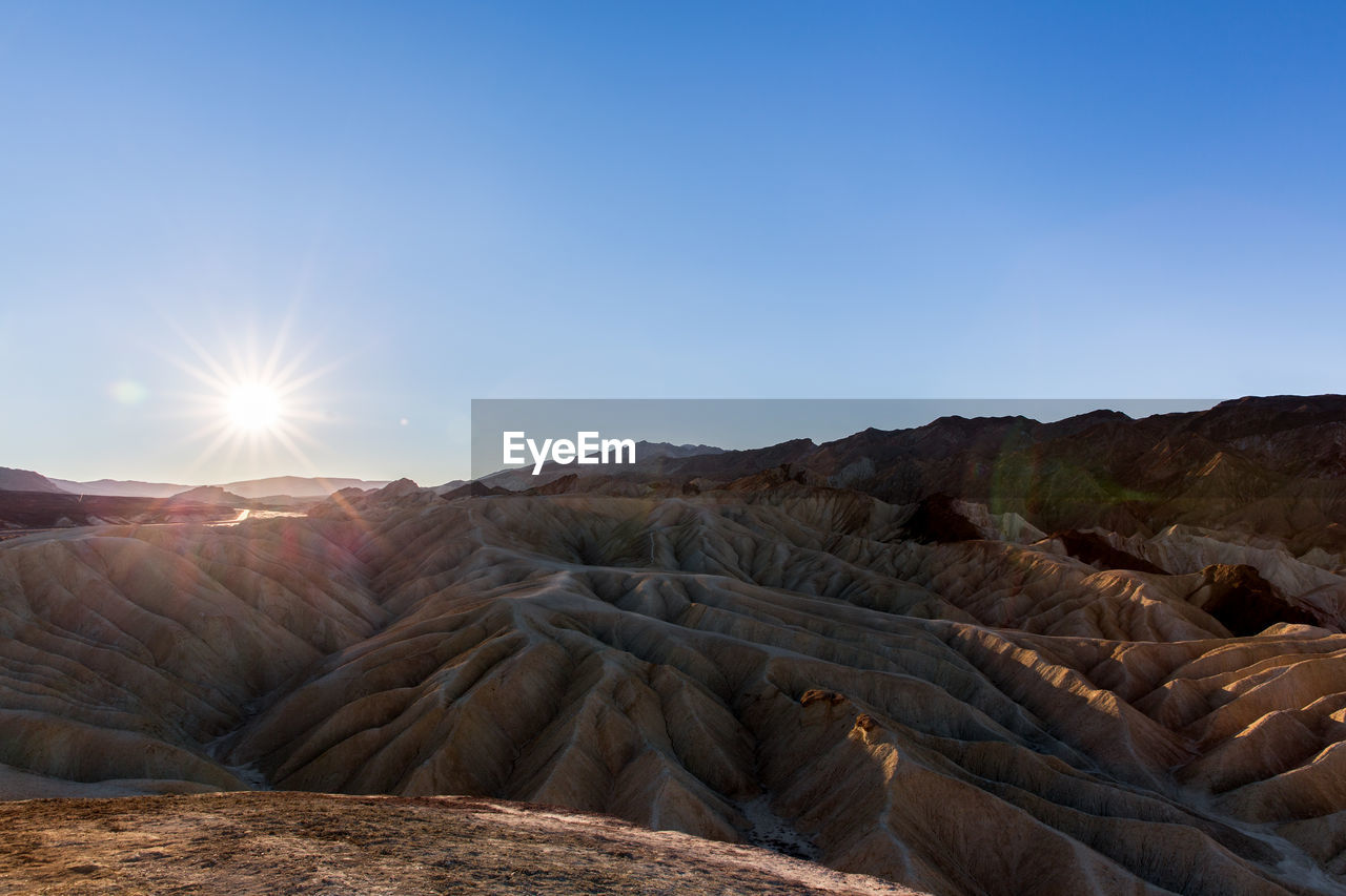 sky, scenics - nature, tranquil scene, beauty in nature, tranquility, non-urban scene, mountain, landscape, environment, sunlight, clear sky, nature, physical geography, no people, rock, geology, copy space, desert, remote, land, sun, arid climate, climate, mountain range, lens flare, outdoors, eroded
