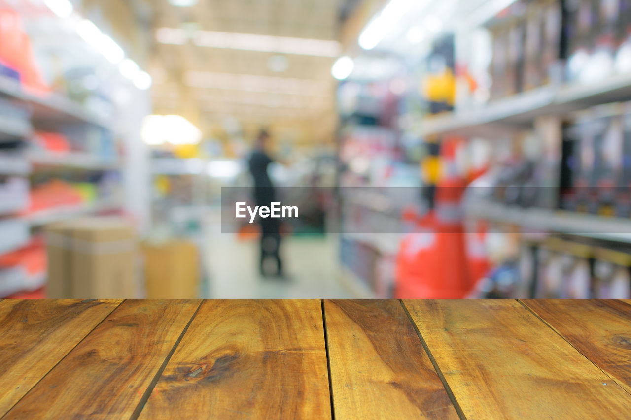 indoors, focus on foreground, real people, one person, retail, shopping, incidental people, lifestyles, wood - material, supermarket, flooring, day, consumerism, store, selective focus, shelf, architecture, business, wood