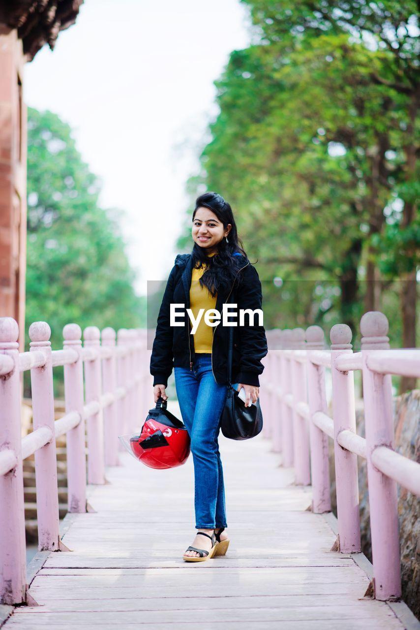 Full Length Portrait Of Woman Standing On Footbridge Against Trees