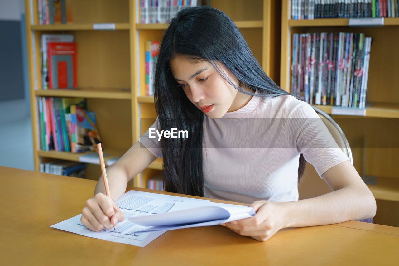 book, publication, table, one person, learning, education, indoors, furniture, concentration, sitting, student, front view, studying, real people, holding, bookshelf, shelf, hair, young adult, hairstyle, teenager
