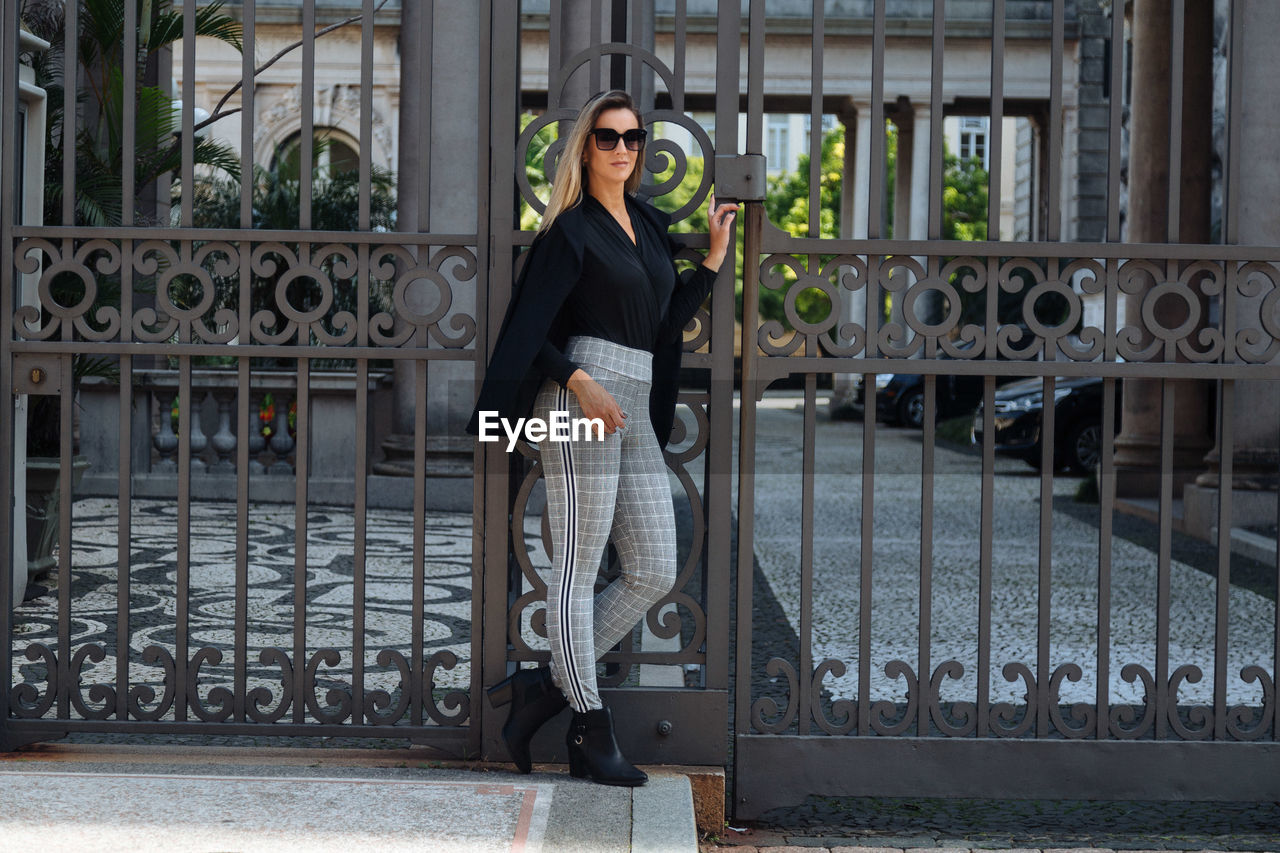 Portrait of woman wearing sunglasses standing against metal gate